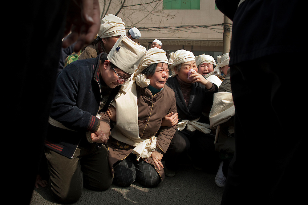 Relatives weep as the coffin of a family member is loaded into a hearse in Zhengzhou, Henan province China.