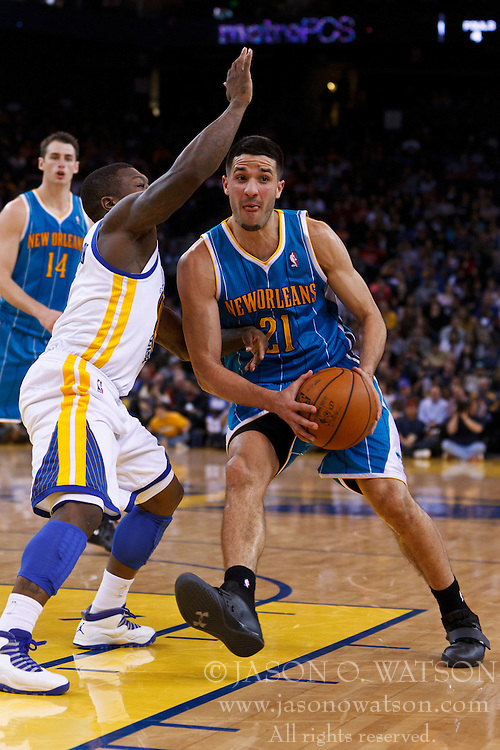 Mar 28, 2012; Oakland, CA, USA; New Orleans Hornets point guard Greivis Vasquez (21) dribbles past Golden State Warriors point guard Nate Robinson (2) during the second quarter at Oracle Arena. Mandatory Credit: Jason O. Watson-US PRESSWIRE