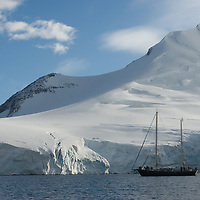 A polar-fitted sailboat anchors by glaciers and mountains on Wiencke Island, near the Antarctic Peninsula, Antarctica.