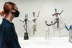 © Licensed to London News Pictures. 13/07/2021. LONDON, UK. A staff member views some of the 17 string puppets (marionettes) made for Carlo Gozzi's King Stag 1918 play.  Preview of the first UK retrospective exhibition at Tate Modern of works by Sophie Taeuber-Arp (1889-1943), one of the foremost abstract artists and designers of the 1920s and 30s. Works from Taeuber-Arp's accomplished career as a painter, architect, teacher, writer, and designer of textiles, marionettes and interiors is on 15 July – 17 October 2021.  Photo credit: Stephen Chung/LNP