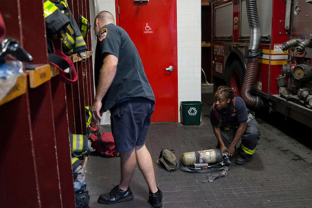 Firefighter Melissa Bennett, right, checks the rig's equipment at the quarters of Engine 257 after a run, 1361 Rockaway Parkway, Brooklyn, NY on Tuesday, Oct. 6, 2015.<br /> <br /> Andrew Hinderaker for The Wall Street Journal<br /> NYFDNY