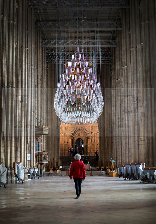 © Licensed to London News Pictures. 24/05/2018. Canterbury, UK.  Artist Monica Guggisberg (in red) walks under a sculpture entitled 'Boat of Remembrance, 2018' - a 20-metre installation of 100 glass amphorae suspended in the shape of a ship high above the Nave of Canterbury  Cathedral. A series of  glass installations by artists Philip Baldwin and Monica Guggisberg reflecting on themes of war and remembrance, migration and refugees are going on display at the cathedral commemorating the 100th anniversary of the end of the First World War. Under an Equal Sky will take visitors on a journey that begins with the Boat of Remembrance in the Nave and ends with a glass wall of multi-coloured vessels in The Crypt . Photo credit: Peter Macdiarmid/LNP