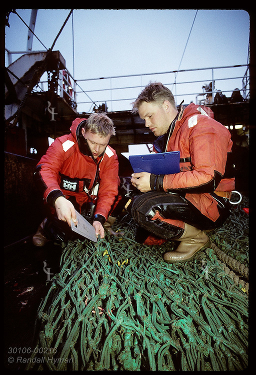 Coast guard inspectors measure net aboard trawler to confirm it is legal; West Fjords. Iceland