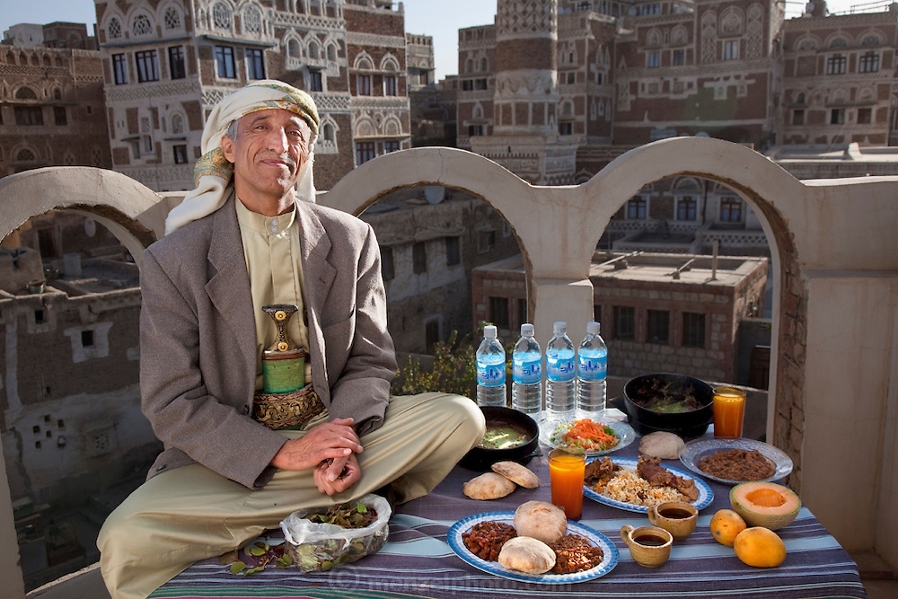 Ahmed Ahmed Swaid, a qat merchant, sits on a rooftop in the old Yemeni city of Sanaa with his typical day's worth of food. (From the book What I Eat: Around the World in 80 Diets.) The caloric value of his typical day's worth of food in the month of April was 3300 kcals. He is 50 years of age; 5 feet, 7 inches tall; and 148 pounds. Ahmed, who wears a jambiya dagger as many Yemeni men do, has been a qat dealer in the old city souk for eight years. Although qat chewing isn't as severe a health hazard as smoking tobacco, it has drastic social, economic, and environmental consequences. When chewed, the leaves release a mild stimulant related to amphetamines. Qat is chewed several times a week by a large percentage of the population: 90 percent of Yemen's men and 25 percent of its women. Because growing qat is 10 to 20 times more profitable than other crops, scarce groundwater is being depleted to irrigate it, to the detriment of food crops and agricultural exports. MODEL RELEASED.