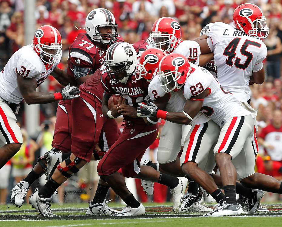 COLUMBIA - SEPTEMBER 11:  Tailback Marcus Lattimore #21 of the South Carolina Gamecocks (center with ball) is tackled by cornerback Brandon Boykin #2 and free safety Jakar Hamilton #23 of the Georgia Bulldogs during the game at Williams-Brice Stadium on September 11, 2010 in Columbia, South Carolina.  The Gamecocks beat the Bulldogs 17-6.    (Photo by Mike Zarrilli/Getty Images)