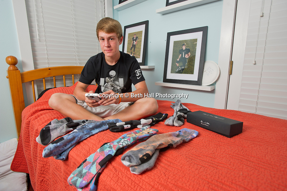 """Winston Robson, 15, of Bentonville, Ark., sits with his sock collection made by Rock """"Em Apparel in his room Tuesday, Sept. 10, 2013, in Bentonville, Ark. Robson owns several pair of the custom Nike Elite socks. Photo by Beth Hall"""