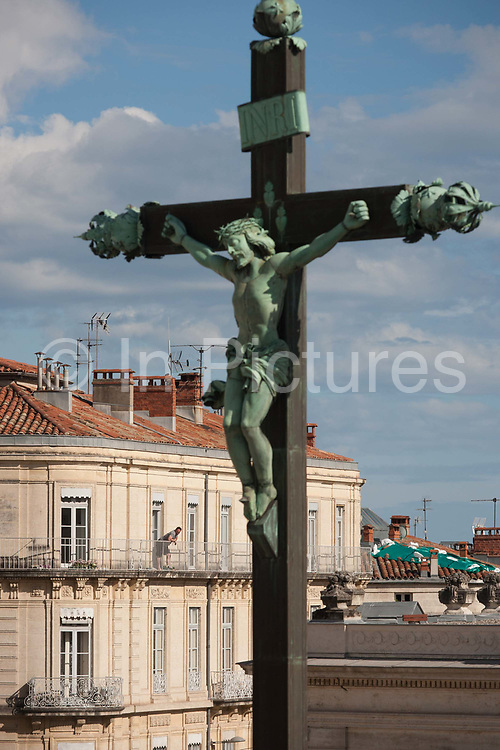 A local resident on the top floor of an apartment building, looks across the town towards by the presence of a crucified Christ on the cross on 18th June 2016, in Montpellier, France. The Christian effigy dominates a street corner on Boulevard Ledru-Rollin, a perimeter ringroad around ancient walls.