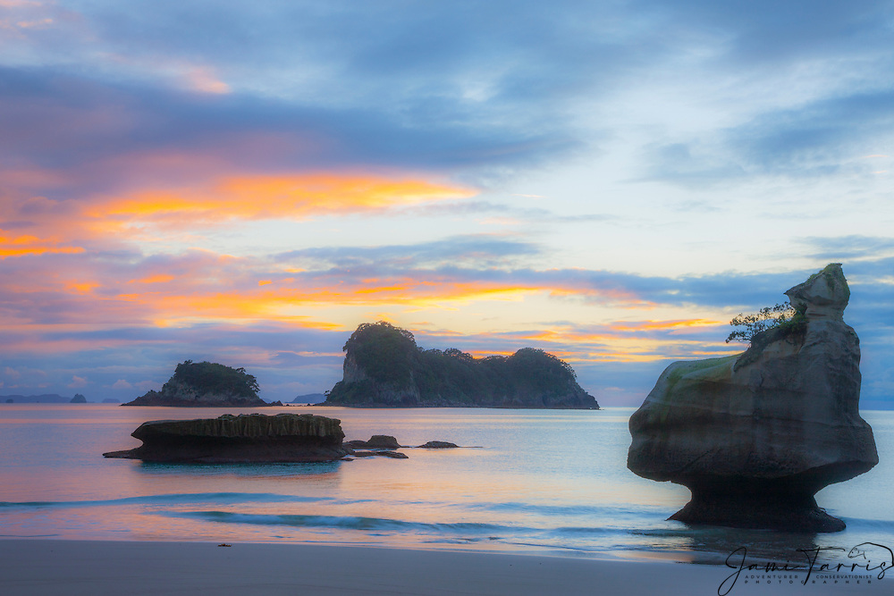 Silhouettes of large rock pinnacles in the ocean off the west coast of the North Island, North Island, New Zealand