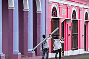 Construction workers walk past colorful colonnade style buildings in Tlacotalpan, Veracruz, Mexico. The tiny town is painted a riot of colors and features well preserved colonial Caribbean architectural style dating from the mid-16th-century.