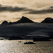 Dramatic snow and ice-covered mountains rise up from the shoreline of the Gerlacht Strait on the western coast of the Antarctic Peninsula as the setting sun casts an orange glow.
