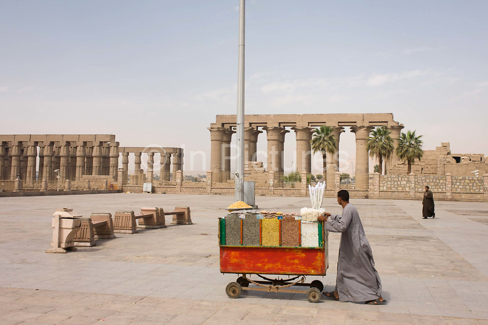 A nuts and seeds stallholder pushes his cart towards just a few arriving tourists during the tourist downturn in front of the ancient Egyptian columns of Luxor Temple, Luxor, Nile Valley, Egypt. According to the country's Ministry of Tourism, European visitors to Egypt is down by up to 80% in 2016 from the suspension of flights after the downing of the Russian airliner in Oct 2015. Euro-tourism accounts for 27% of the total flow and in total, tourism accounts for 11.3% of Egypt's GDP. The temple was built by Amenhotep III, completed by Tutankhamun then added to by Rameses II. Towards the rear is a granite shrine dedicated to Alexander the Great and in another part, was a Roman encampment. The temple has been in almost continuous use as a place of worship right up to the present day.