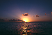 Clouds and rays and sunset and sailboat from Antigua looking towards the island of Montserrat in the Caribbean