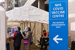 © Licensed to London News Pictures. 18/01/2021. LONDON, UK.  People arrive at a vaccination at the Olympic Office Centre in Wembley, north London.  This is one of ten new mass Covid vaccination centres opening today and they join the seven already in use across the country.  So far, 3.8 million people across the UK have received a first dose and the government hopes that number to rise to 15 million by 15 February.  Photo credit: Stephen Chung/LNP
