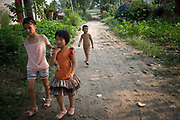 Young children walk down a road in rural village near Fuyang, Anhui Province,  China on 28 August  2013.  As able-bodied adults seek work in cities in hopes of better income, more and more villages in China are inhabited mostly by the elderly and children.