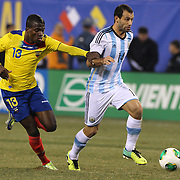 Javier Mascherano, (right), Argentina, is challenged by Enner Valencia, Ecuador, during the Argentina Vs Ecuador International friendly football match at MetLife Stadium, New Jersey. USA. 15th November 2013. Photo Tim Clayton