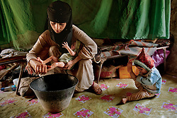 Asia, 14, washes her newborn at home in Hajjah while her 2-year-old daughter plays. Asia is still bleeding and ill from childbirth, yet has no knowledge of how to care for herself nor access to maternal health care.