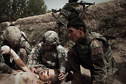 US soldiers and officers from 1-75 CAV 101st Airborne Division tend to the life-threatening injuries of one their own after he was wounded when a remote-controlled IED was detonated as a group of US and Afghan soldiers were entering the Kandahari village of Zenadan in the province's Zhari District on Sept. 17, 2010. The IED - which appears to have been detonated in a deliberate attempt to kill an US and Afghan lieutenant colonel who were in the column - also killed an Afghan soldier