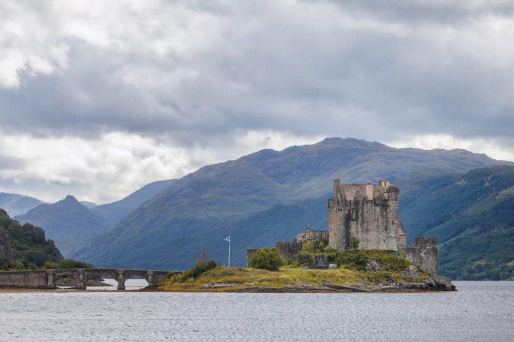 Eilean Donan offers one of the most iconic images of Scotland. It is situated on an island at the point where three great sea lochs meet, and surrounded by some majestic scenery.<br /> <br /> First inhabited around the 6th century, the first fortified castle was built in the mid 13th century and stood guard over the lands of Kintail. Since then, at least four different versions of the castle have been built and re-built as the feudal history of Scotland unfolded through the centuries.<br /> <br /> Partially destroyed in a Jacobite uprising in 1719, Eilean Donan lay in ruins for the best part of 200 years until Lieutenant Colonel John MacRae-Gilstrap bought the island in 1911 and proceeded to restore the castle to its former glory. After 20 years of toil and labour the castle was re-opened in 1932.<br /> <br /> This photograph is a colour close view of Eilean Donan Castle from the north, on Loch Alsh through to Loch Duich. The photograph can be purchased as print, mounted print in frames, canvas or aluminum or as a digital file.