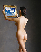 Rear view of nude woman holding a gilt picture frame with a photo of clouds