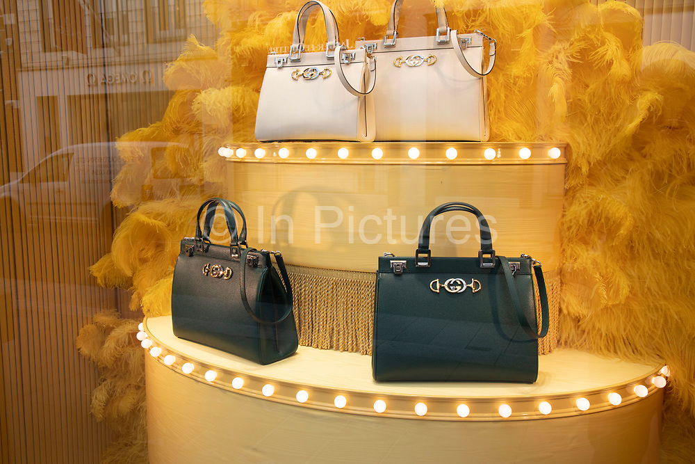 Hand bags in exclusive clothes shop window for Gucci on New Bond Street in Mayfair, London, England, United Kingdom. Bond Street is one of the principal streets in the West End shopping district and is very upmarket. It has been a fashionable shopping street since the 18th century. The rich and wealthy shop here mostly for high end fashion and jewellery.