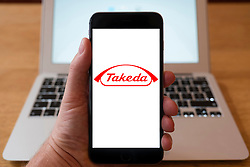 Using iPhone smartphone to display logo of Takeda, a Japanese pharmaceutical company