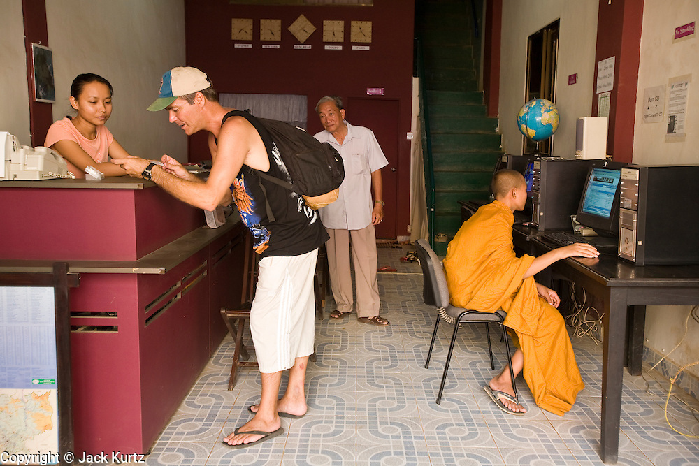26 JUNE 2006 - SIEM REAP, CAMBODIA: A tourist pays his bill while a Buddhist monk uses a computer in an internet cafe near the main market in Siem Reap, Cambodia, site of the world famous Angkor Wat. Photo by Jack Kurtz / ZUMA Press