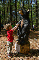 Jason introduces himself to the bear critter in Prescott Farm's Natural Playscape during the grand opening on Saturday morning.  (Karen Bobotas/for the Laconia Daily Sun)