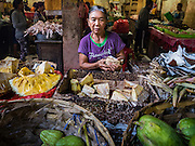 11 OCTOBER 2016 - UBUD, BALI, INDONESIA: A fruit vendor in the morning market in Ubud. The morning market in Ubud is for produce and meat and serves local people from about 4:30 AM until about 7:30 AM. As the morning progresses the local vendors pack up and leave and vendors selling tourist curios move in. By about 8:30 AM the market is mostly a tourist market selling curios to tourists. Ubud is Bali's art and cultural center.      PHOTO BY JACK KURTZ