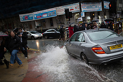 © Licensed to London News Pictures . 12/12/2015 . Manchester , UK . A car splashing through standing water in Piccadilly as people shop in the rain in Manchester City Centre this afternoon (Saturday 12th December 2015 ) . Photo credit : Joel Goodman/LNP