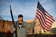 Tony Murphy poses with an American flag and shotgun during an open carry long rifle march demonstrating his 2nd amendment right to keep and bear arms on Thursday, January 31, 2013 in Fort Worth, Texas. (Cooper Neill/The Dallas Morning News)