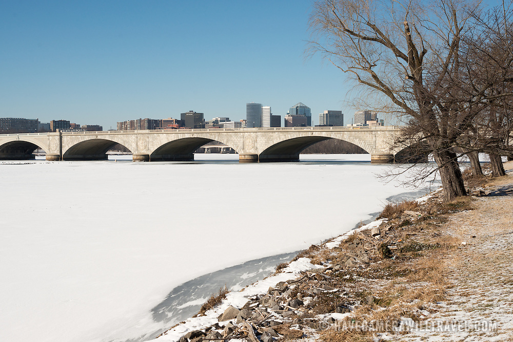Arlington Memorial Bridge spans an expanse of ice and snow-covered Potomac from Washington DC across to Arlington Virginia, with the buildings of Rosslyn visible in the distance. The Potomac running through Washington DC is frozen and covered with a layer of snow. The region has experienced an unusually cold winter, with sustained low temperatures.
