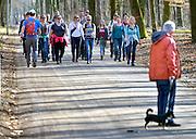 Nederland, Nijmegen, 8-3-2015Onder leiding van een cursusleider, gids maken wandelaars een wandeling door stadspark de Goffert. de groep loopt in het gelid en moet van de docent de goede loophouding aannemen. Buurtbewoners die de hond uitlaten kijken toe. Foto: Flip Franssen/Hollandse Hoogte