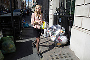 Woman walking past a pile of rubbish recycling bags lying on the street outside in Mayfair, London, UK.