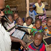 Kids at Koumbadiouma's primary school clamber over one another to show their teacher their work. Kolda, Senegal.