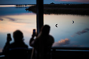 People photograph the sunset over Currituck Sound while birds sit on the water in Corolla, North Carolina on Friday, January 8, 2021.