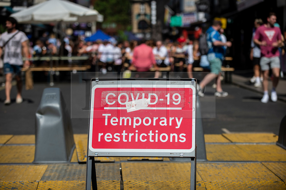 © Licensed to London News Pictures. 12/06/2021. LONDON, UK. A Covid-19 temporary restrictions sign in Soho.  Scientific advisers to the UK government have called for a delay to the complete lifting of coronavirus lockdown restrictions on 21 June, possibly by four weeks, to allow scientists to assess the link between rising numbers of Covid-19 cases (mainly the newly identified Delta variant) and hospital admissions.  Photo credit: Stephen Chung/LNP