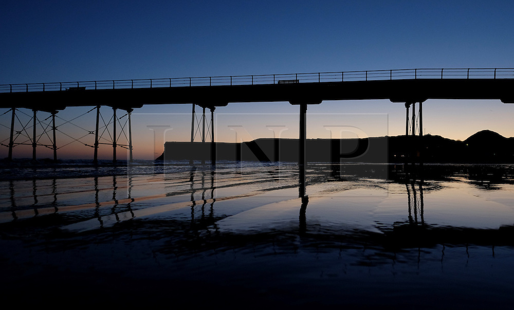 (c) Licensed to London News Pictures. 04/12/2015<br /> Saltburn. UK. <br /> Saltburn pier can be seen reflecting in wet sand as the first light of day rises up over the cliffs of Huntcliff.<br /> Photo credit : Ian Forsyth/LNP