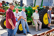 """06 AUGUST 2020 - FAIRFIELD, IOWA: People lean against a John Deere 4020 tractor and watch the bidding during the auction on the Adam Farm near Fairfield. Gary Adam, 72 years old, has been farming in the Fairfield area since 1971. He decided to retire this year because he wants to travel and because it's so difficult to make money in farming this year. He said he wants to """"shed the risk and responsibility. If things were super good, like they were 2006-2012, I might stay in it, but they're not."""" Adam did not sell the tractor because it was the first tractor he bought when he started farming. The 4020 tractor was produced from 1964 to 1972. An increasing number of farmers in the Midwest are retiring this year as it becomes harder to make money on crops. In addition to low prices, Iowa farmers are being hit with a drought this year, with well below average rain over most of the state. Because of the COVID-19 pandemic, the auction on Adam's farm was one of the first live in person auctions since winter. Most auctions are now done on line.   PHOTO BY JACK KURTZ"""
