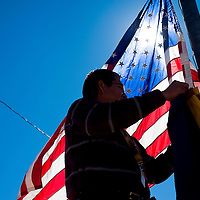 101312       Cable Hoover<br /> <br /> Window Rock Unified School District employee Jonah Yazzie removes the flags from the flagpole in front of the Fort Defiance Fieldhouse following a volleyball match their Saturday.
