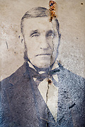 cracked photograph with portrait of an adult man early 1900s