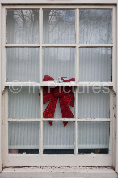 Weeks after Christmas, the remains of an xmas ribbon decoration  still hangs in the box sash window of a house in central London, on 11th January 2017, in London, England.