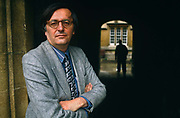 With a shadowy person in the background, John Gray the political scientist, stands with arms folded and wearing a grey jacket and his round-frame glasses in the Quadrangle of Jesus College, Oxford, amid classical architecture. He is a prominent British political philosopher, author and currently School Professor of European Thought at the London School of Economics. Prior to this he was Professor of Politics at Oxford University. He is a former supporter of the New Right and a regular contributor to the Guardian and the Times Literary Supplement. Also author of many books on political theory. He has written several influential books on political theory, including Straw Dogs: Thoughts on Humans and Other Animals (2003), an attack on humanism, a worldview which he sees as originating in religious ideologies.
