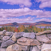 A stone wall in autumn. Moosehead Lake in Greenville Maine.