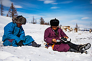 Tsaatan reindeer herders taking a rest break from walking their reindeer (Rangifer tarandus) in deep snow in the mountains and taking a cup of wine, Khovsgol Province, Mongolia