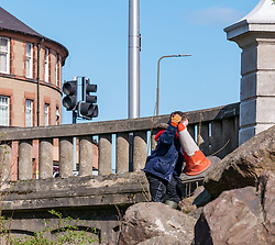 Pictured: Water of Leith Spring clean, Edinburgh, Scotland. 31 March 2019. A group of volunteers does an annual Spring clean along a section of the banks of the Water of Leith which runs through Edinburgh, organised by the Water of Leith Conservation Trust. A young boy retrieves a traffic cone from the riverbank<br /> Sally Anderson | EdinburghElitemedia.co.uk<br /> Reproduction fee payable to Edinburgh Elite Media