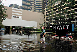 30 August, 2005. New Orleans Louisiana.  Hurricane Katrina aftermath. <br /> Photographer Rick Hannon of the Baton Rouge Advocate wades through flood water at the Hyatt Hotel in downtown New Orleans.<br /> Photo Credit: Charlie Varley/varleypix.com