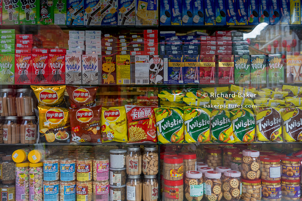 A detail of assorted snacks including biscuits, crisps and other merchandise on shelves in a corner shop (convenience store) window on Gerrard Street, Chinatown, on 5th March 2018, in London, England.