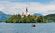 A rowboat approaches the medieval church on glacially formed Lake Bled (Slovene: Blejsko jezero) in the Julian Alps in northwestern Slovenia, Europe. The lake surrounds Bled Island (Blejski otok, the only natural island in Slovenia), upon which stands the Pilgrimage Church of the Assumption of Mary (Slovenian: Cerkev Marijinega vnebovzetja), built in the 15th century and now popular for romantic weddings. Lake Bled hosted the World Rowing Championships in 1966, 1979, 1989, and 2011. The lake is 35 kilometers from Ljubljana International Airport.