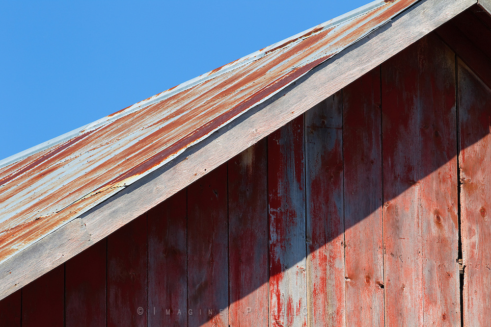 Faded red paint and rusting tin roof.