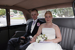 Bride and groom sitting in back of chauffeur driven car,